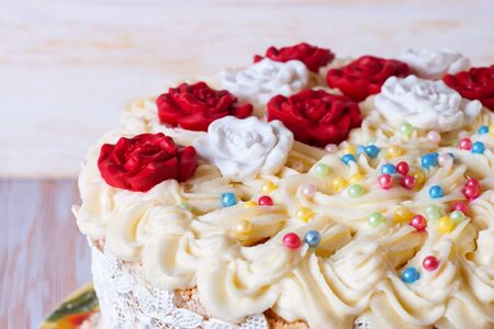 white cake with cream and red roses on white wooden backghound. close up photo.