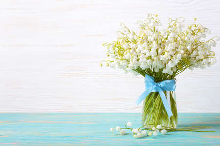 bouquet of lilies of the valley in a vase with blue ribbon on a blue and white wooden background Stockfoto
