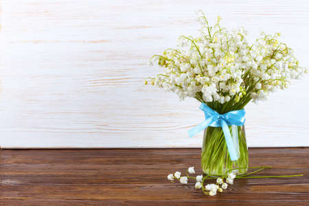 bouquet of lilies of the valley in a vase with blue ribbon on a brown and white wooden background Stockfoto