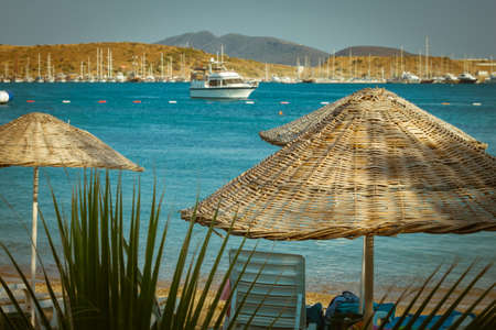 Thatched sun umbrellas, beach umbrellas on the sea background with blurred yachts. color tonal effect.