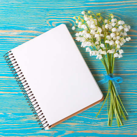 Bouquet of flowers lily of the valley and empty paper notebook on blue rustic table.