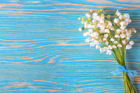 Bouquet of lilies of the valley on the wooden background
