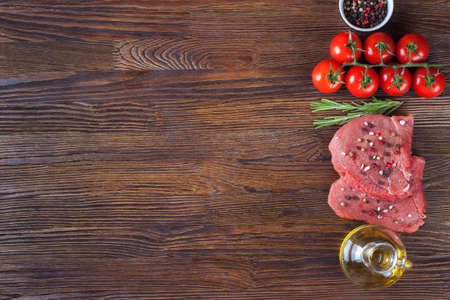 Raw steak with spices and ingredients for cooking. Flat lay. Top view.