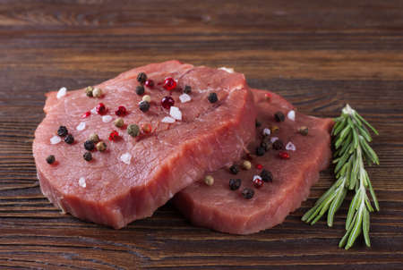 raw beef steak with rosemary on brown wooden background