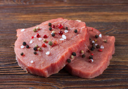 raw beef steak with spice on brown wooden background