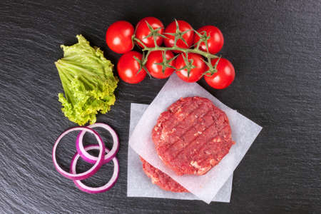 The raw ingredients for the homemade burger. Two raw coutlet on paper, tomatoes, salad, onion rings on black slate background. Top view. Flat lay. Фото со стока