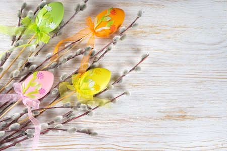 Willow tree branch with colorful eggs easter decoration on white wooden background