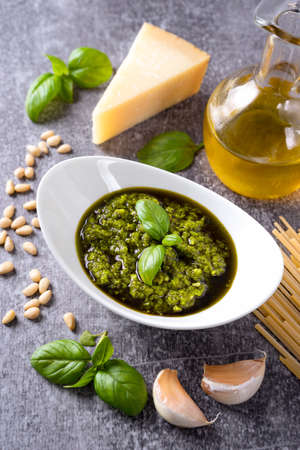 Homemade pesto sause with food ingredients on gray background