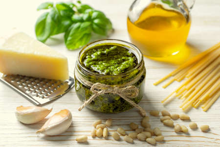 Homemade pesto sause with food ingredients on white wooden background