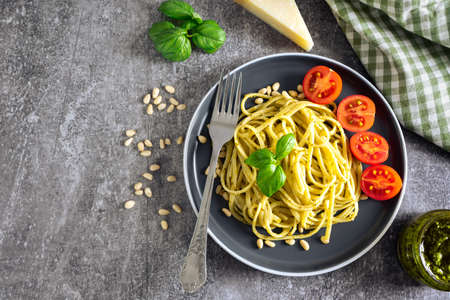 Pasta pesto with fork on grey concrete background. Flat lay with copy space. Traditional italian spaghetti and food ingredients pesto sauce, tomato, parmesan, pine nuts, fresh basil leaves