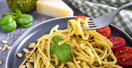 Pasta pesto with fork on grey concrete background. Traditional italian spaghetti with food ingredients pesto sauce, tomato, parmesan cheese, pine nuts, fresh basil leaves. close up banner. Stock Photo