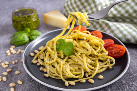 Pasta pesto with fork on grey concrete background. Traditional italian spaghetti with food ingredients pesto sauce, tomato, parmesan cheese, pine nuts, fresh basil leaves