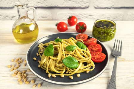 Pasta pesto with fork and fresh pesto sauce on white wooden background. Traditional italian spaghetti and food ingredients pesto sauce, tomato, parmesan, pine nuts, fresh basil leaves Stock Photo