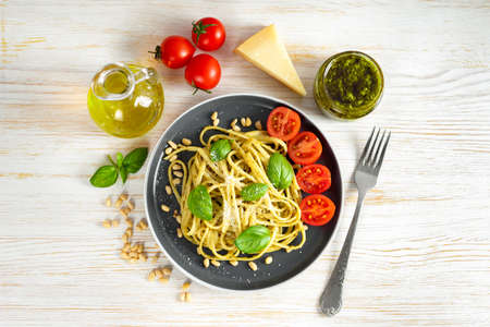 Pasta pesto with fork and fresh pesto sauce on white wooden background. Traditional italian spaghetti and food ingredients pesto sauce, tomato, parmesan, pine nuts, fresh basil leaves. Flat lay