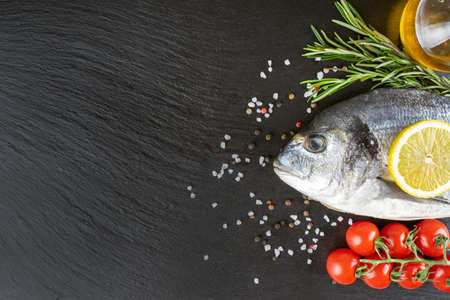 Raw fish dorado on black slate background with spices, tomato, rosemary, olive oil and lemon. Top view, flat lay with copy space for text Stock Photo