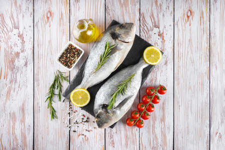 Raw fish dorado on black slate cutting board and white wooden background with spices, tomato, rosemary, olive oil and lemon. Top view, flat lay with copy space for text
