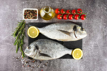 Raw fish dorado on black slate cutting board and grey concrete background with spices, tomato, rosemary, olive oil and lemon. Top view, flat lay with copy space for text