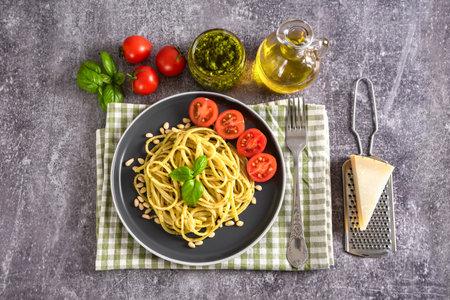 Pasta pesto with fork and fresh pesto sauce on grey concrete background. Traditional italian spaghetti and food ingredients pesto sauce, tomato, parmesan, pine nuts, fresh basil leaves