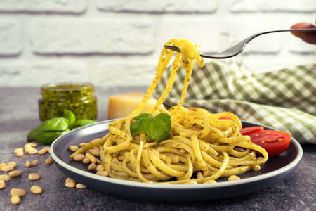 Pasta pesto with fork in dark plate on grey concrete background. Traditional italian spaghetti with food ingredients pesto sauce, tomato, parmesan cheese, pine nuts, fresh basil leaves