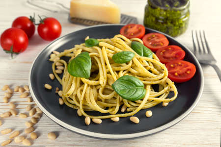 Pasta pesto with fork on white wooden background. Traditional italian spaghetti with food ingredients pesto sauce, tomato, parmesan cheese, pine nuts, fresh basil leaves