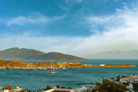 View of the bay of Bodrum, Turkey with yacht and mountains in a beautiful sunny day with cloudy blue sky. Summer landscape, travel destination