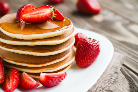 freshly prepared: stack of freshly prepared traditional pancakes with strawberries and honey on a old wooden table