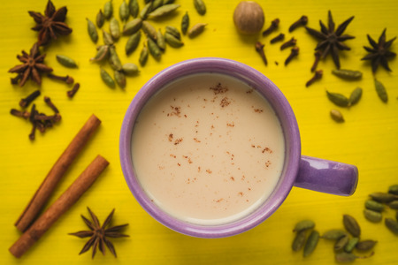 masala chai: masala chai tea with spices and star Anise, cinnamon stick, nutmeg, and cardamon on the yellow background