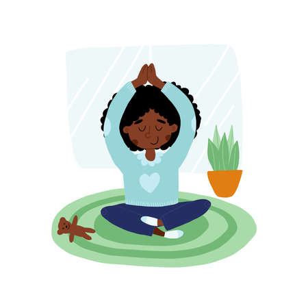 Cute African American girl put down a toy and meditates in lotus or padmasana pose with hands up above her head.