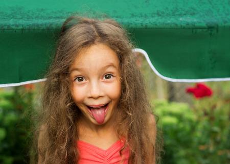 sacar la lengua: Retrato de una ni�a adorable con la lengua fuera Foto de archivo