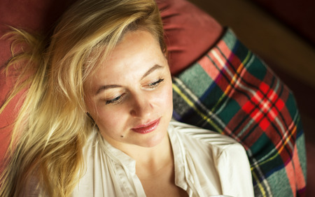 Thoughtful young woman lying on sofa at home photo