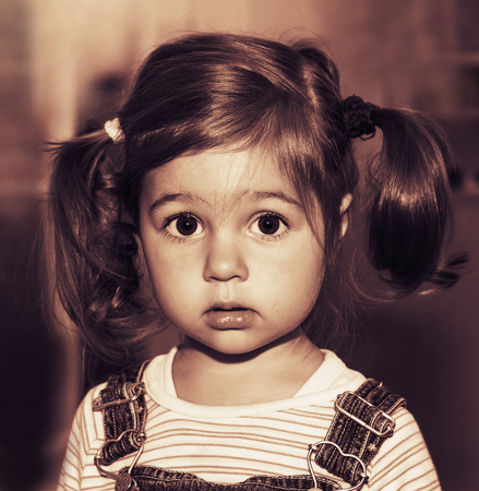 portraits: Portrait of cute sad little girl thinking. Toned