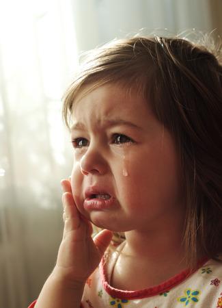 かわいい小さな子供が泣いています。
