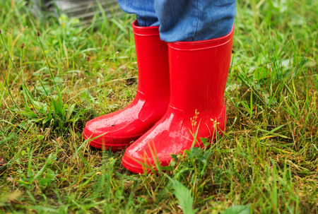 kid feet: Close up of kid feet walking in red boots in green grass
