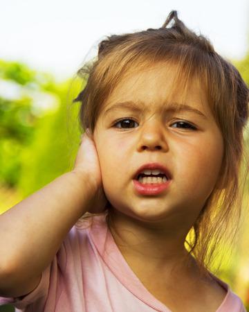 cute little girl holding her hand at the ear Standard-Bild