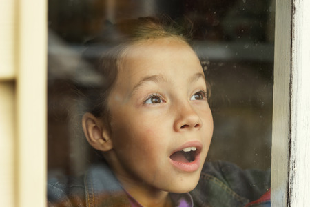 looking through window: happy little girl looking through an old window