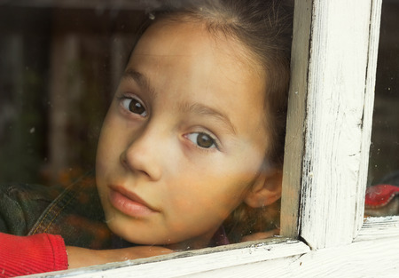 sad little girl looking through an old window photo