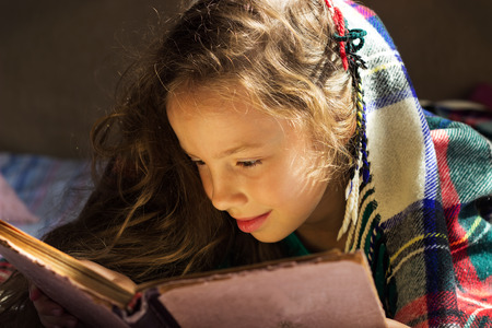 portrait of cute curly school girl reading an old book at cold day Stock Photo