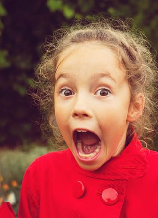 mouths: Little girl in red jacket is shocked and surprised and so happy about it. Stock Photo