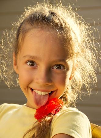sacar la lengua: chica linda escuela con la lengua fuera en un d�a soleado Foto de archivo