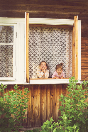 blab: two happy cute girls smiling in window at home
