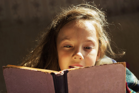 portrait of cute curly girl reading book