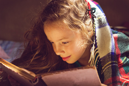 niños leyendo: Vintage retrato de linda chica de la escuela rizado leyendo un libro en día frío Foto de archivo