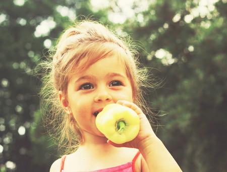 Toned portrait of Little girl eating pepper
