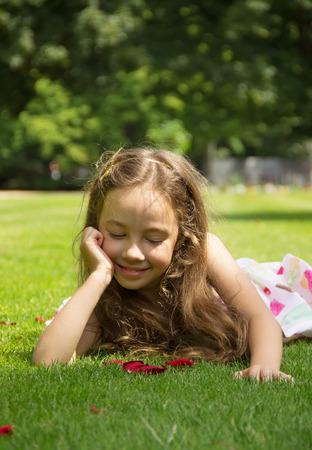 Pretty little girl resting on a green grass photo