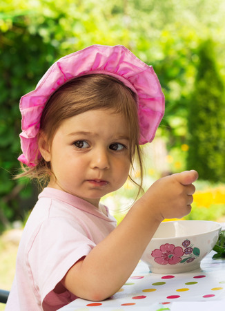 purpule: portrait of little cute girl in a purpule cap eats with appetite a breakfast from a plate with the drawn flower in outdoor cafe