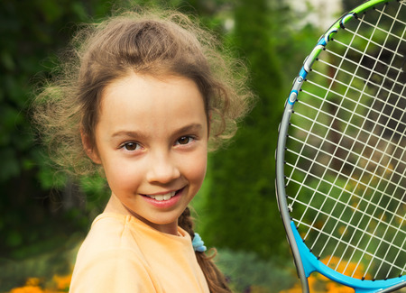 portrait of cute little girl playing tennis in summer photo
