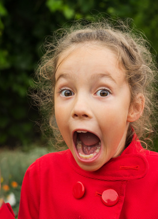 disbelieve: Little girl in red jacket is surprised and so happy about it.