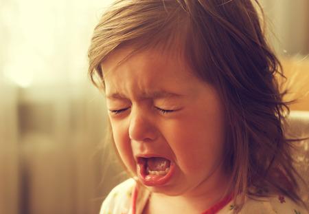 かわいい小さい子供が泣いています。