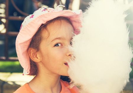Cute girl with white cotton candy.  photo