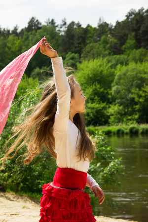 gentle dream vacation: portrait of curly girl dance with pink Scarf at the river